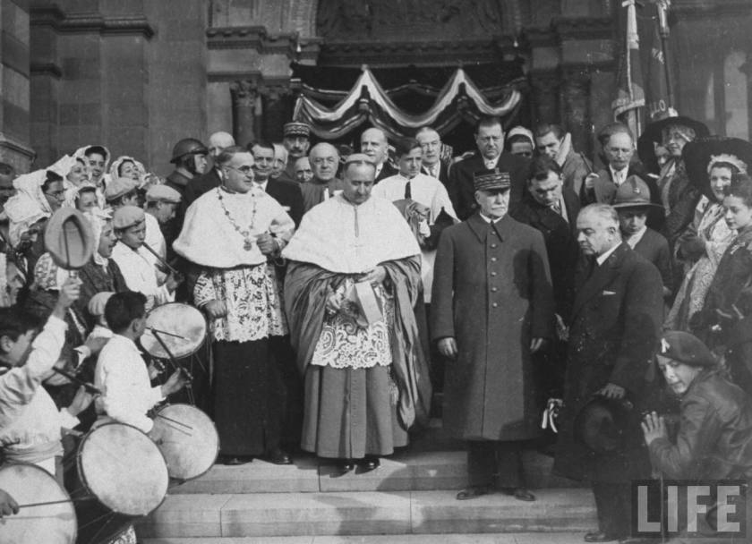 Vichy Chief of State Phillipe Pétain (long coat & military cap) standing on steps beside clergy of Cathedral at Marseille, after offering prayer in service for war dead
